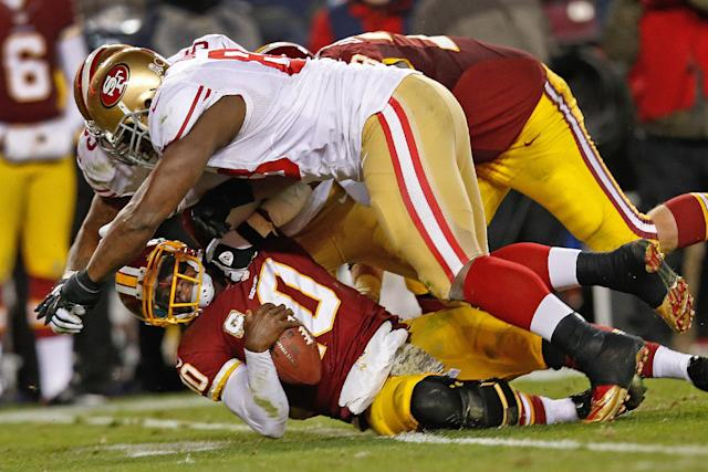 Washington Redskins quarterback Robert Griffin III is knocked to the turf by San Francisco 49ers tight end Demarcus Dobbs, front, and another defender during the second half of an NFL football game in Landover, Md., Monday, Nov. 25, 2013. The 49ers deafeted the Redskins 27-6. (AP Photo/Alex Brandon)
