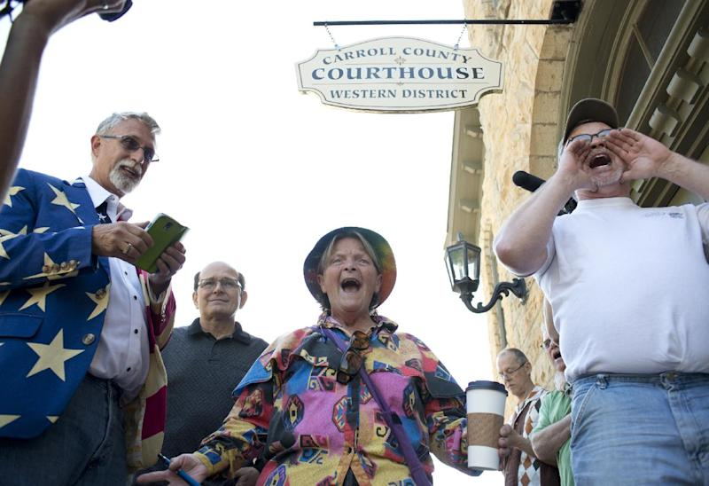 Sheila McFadden, center, and Ken Riley, right, yell words of encouragement at the crowd gathered in front of the Carroll County Courthouse after initially being turned away for a marriage license in Eureka Springs, Ark., Saturday, May 10, 2014, in Eureka Springs, Ark. Same-sex couples were eventually granted marriage licenses, Saturday, in Eureka Springs after a judge overturned Amendment 83, which banned same-sex marriage in the state of Arkansas. (AP Photo/Sarah Bentham)