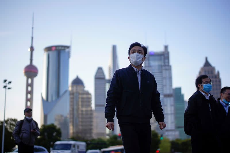 FILE PHOTO: People wear protective face masks, following an outbreak of the novel coronavirus disease (COVID-19), at Lujiazui financial district in Shanghai