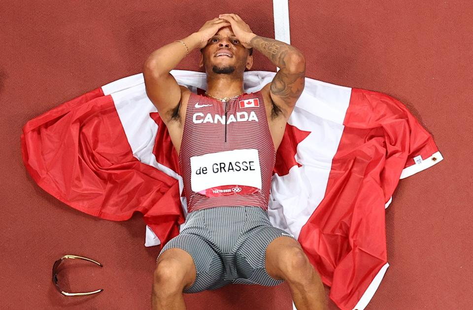 Andre De Grasse lies down on the track with his head in his hands after winning his first gold medal as an Olympian in Tokyo.