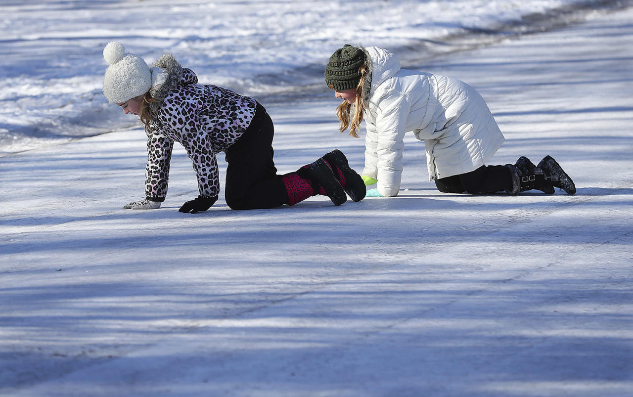 <p>Kaylee Collins, left, and her friend Lana Anderson, both 9, crawl on their hands and knees rather than risk falling while crossing ice covered Pine Terrace Road in Cherokee Falls Estates at the Lake subdivision playing in the aftermath of the storm on Jan. 8, 2017, in Canton. (Photo: Curtis Compton/Atlanta Journal-Constitution via AP) </p>