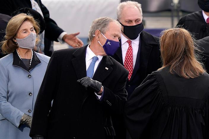 <p>George W. Bush and Supreme Court Justice Amy Coney Barrett tap elbows at the inauguration. </p>