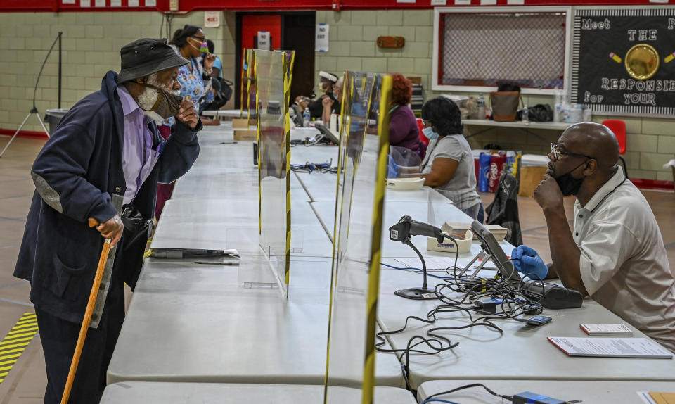 Voter Wayne Polston, left, has to briefly lower his mask in order to be understood by an election judge at Edmondson Westside High School during the primary election in Baltimore, Tuesday, June 2, 2020. (Jerry Jackson/The Baltimore Sun via AP)