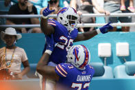 Buffalo Bills running back Devin Singletary (26) is lifted by Buffalo Bills offensive tackle Dion Dawkins (73) after scoring a touchdown during the first half of an NFL football game, Sunday, Sept. 19, 2021, in Miami Gardens, Fla. (AP Photo/Wilfredo Lee)
