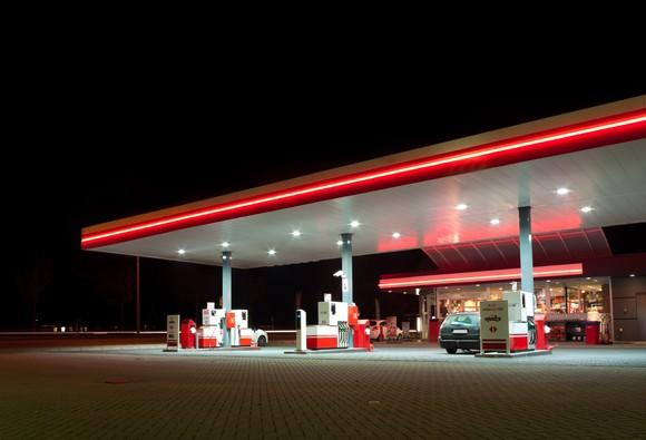 Gas station and convenience store illuminated at night.