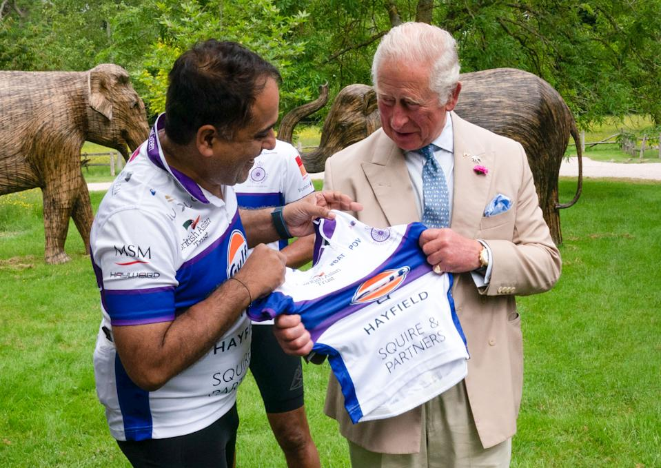 Rohit Chadda presents the Prince of Wales with a cycling vest, which was two sizes too small, before he joined representatives of the British Asian Trust at Highgrove in Gloucestershire before they embark on the charity's 'Palaces on Wheels' cycling event. Picture date: Thursday June 10, 2021.