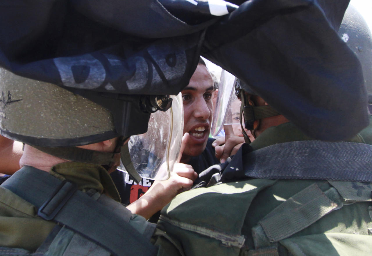 "A Palestinian protester argues with Israeli border policemen during a rally to commemorate the 1948 creation of the Israel state known in Arabic as the ""Nakba Day"", or ""Day of the Catastrophe"" outside the West Bank town of Bethlehem, Tuesday, May 14, 2013. (AP Photo/Nasser Shiyoukhi)"