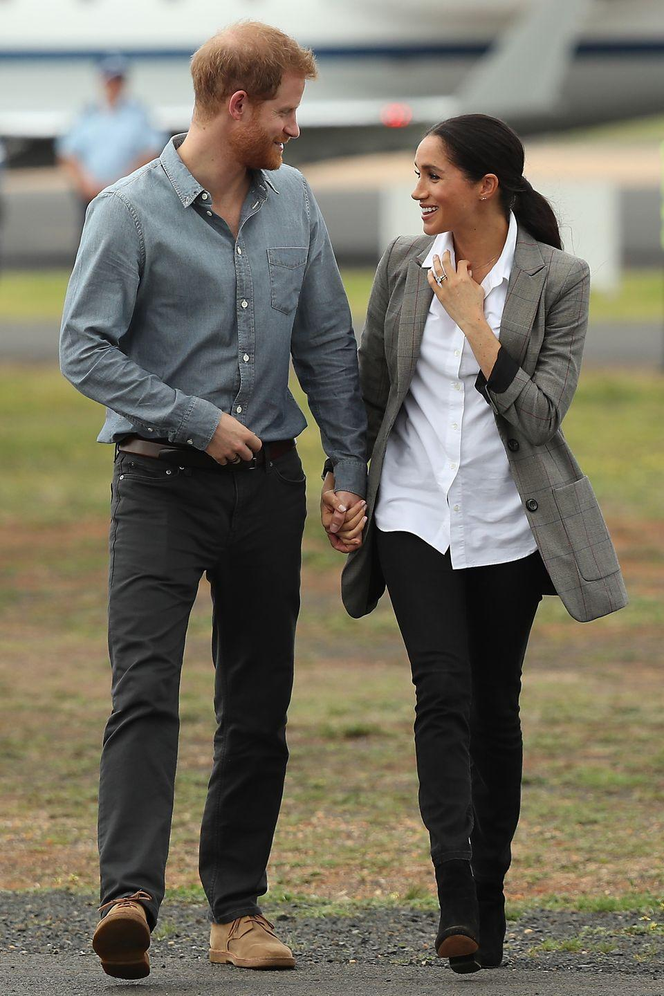 """<p>Arriving in Dubbo, Australia with Prince Harry, Meghan wore a white button-down from the brand Maison Kitsuné.</p><p><a class=""""link rapid-noclick-resp"""" href=""""https://go.redirectingat.com?id=74968X1596630&url=https%3A%2F%2Fwww.ssense.com%2Fen-us%2Fwomen%2Fproduct%2Fmaison-kitsune%2Fwhite-fox-head-embroidery-classic-shirt%2F6961641&sref=https%3A%2F%2Fwww.townandcountrymag.com%2Fsociety%2Ftradition%2Fg36386449%2Fmeghan-markle-white-button-down-shirts%2F"""" rel=""""nofollow noopener"""" target=""""_blank"""" data-ylk=""""slk:Shop Now"""">Shop Now</a></p>"""