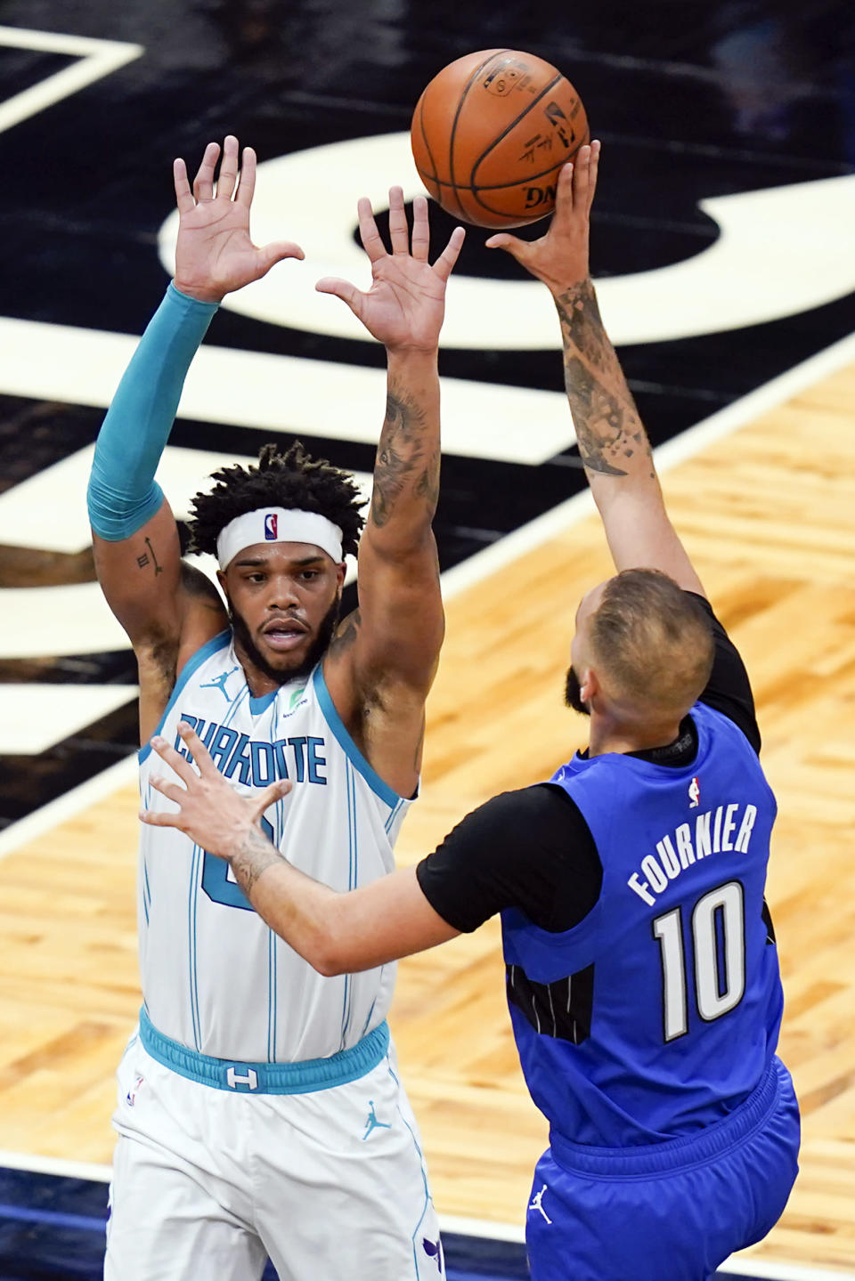 Orlando Magic guard Evan Fournier, right, takes a shot over Charlotte Hornets forward Miles Bridges, left, during the first half of an NBA basketball game, Sunday, Jan. 24, 2021, in Orlando, Fla. (AP Photo/John Raoux)