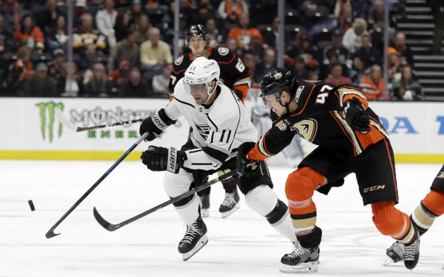 Los Angeles Kings' Anze Kopitar, left, is defended by Anaheim Ducks' Hampus Lindholm during the first period of an NHL hockey game Friday, April 5, 2019, in Anaheim, Calif. (AP Photo/Marcio Jose Sanchez)