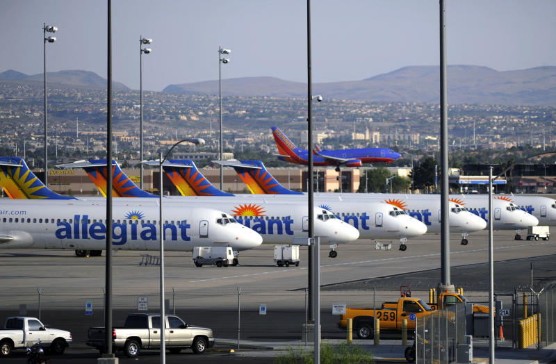 In this Thursday, May 9, 2013, photo, a Southwest airliner comes in for a landing as a row of Allegiant Air jets are parked at McCarran International Airport in Las Vegas. While other U.S. airlines have struggled with the ups and downs of the economy and oil prices, tiny Allegiant Air has been profitable for 10 straight years. (AP Photo/David Becker)