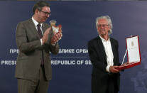 Austrian author Peter Handke, right, receives the Order of the Karadjordje's Star from Serbian President Aleksandar Vucic in Belgrade, Serbia, Sunday, May 9, 2021. Serbia has decorated Austrian Nobel literature laureate Peter Handke, who is known for his apologist views over Serb war crimes during the 1990s' wars in the Balkans. (AP Photo/Darko Vojinovic)