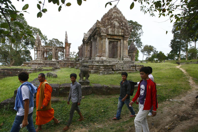 A Cambodian Buddhist monk, second from left, walks together with local tourists through the famed Preah Vihear temple near Cambodia-Thai border in Preah Vihear Province, Cambodia, Sunday, Nov. 10, 2013. The International Court of Justice rules on a dispute between Cambodia and Thailand over land surrounding the 1,000-year-old temple on Monday. (AP Photo/Heng Sinith)