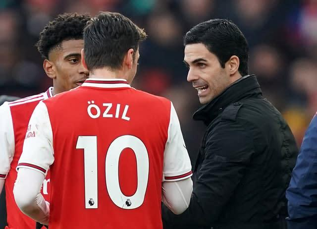 Mesut Ozil, left, has been challenged to keep working hard by new boss Mikel Arteta, right (John Walton/PA)