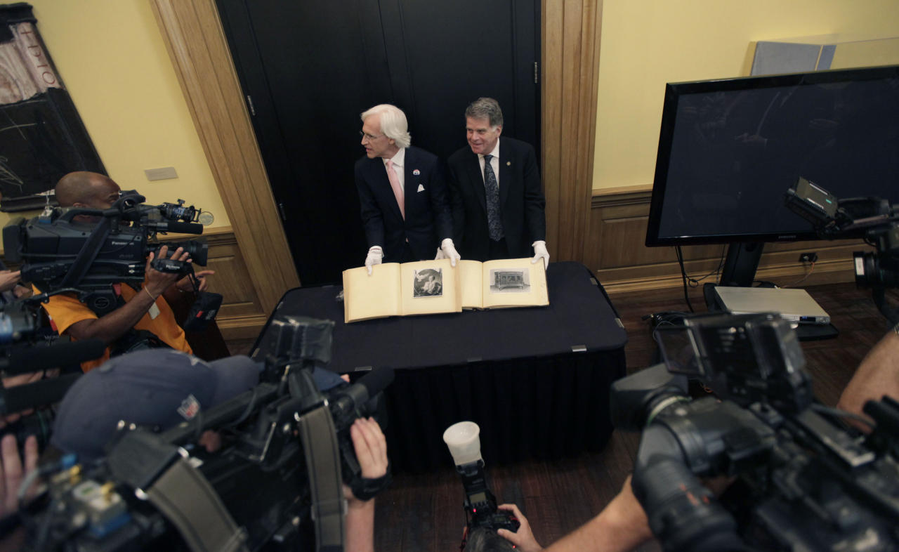 David S. Ferriero, archivist of the United States, right, and Robert M. Edsel, founder and president of Monuments Men Foundation for the Preservation of Art show to media two newly discovered albums containing photographs of art works and furniture stolen by the Nazis during World War II after they were unveiled at a news conference in the Meadows Museum at SMU in Dallas, Tuesday, Feb. 27, 2012. The Dallas-based Monuments Men Foundation for the Preservation of Art had been contacted by relatives of two World War II soldiers who took the albums from Hitler's home. They'll be donated to the U.S. National Archives. (AP Photo/LM Otero)