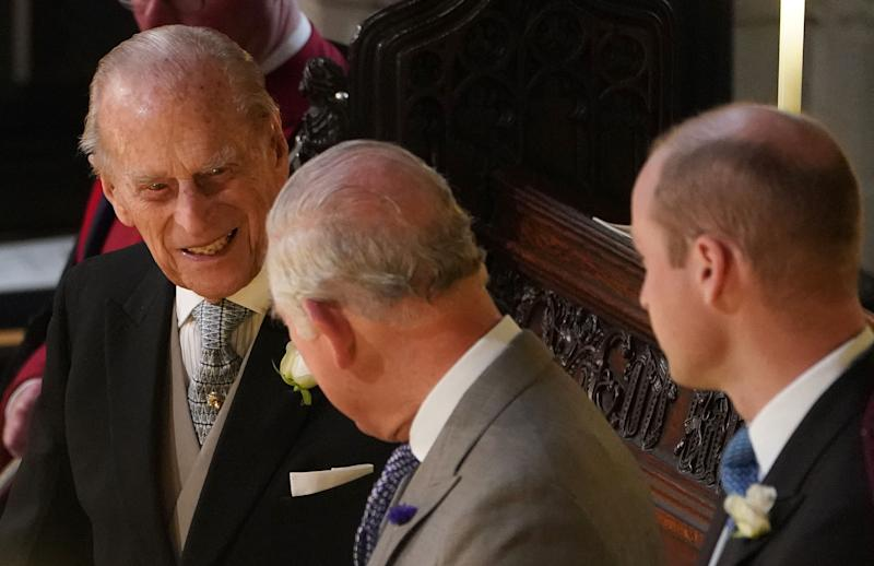 Britain's Prince Philip, Duke of Edinburgh (L), Britain's Prince Charles, Prince of Wales (C) and Britain's Prince William, Duke of Cambridge, react during the wedding ceremony of Britain's Princess Eugenie of York to Jack Brooksbank at St George's Chapel, Windsor Castle, in Windsor, on October 12, 2018. (Photo by Owen Humphreys / POOL / AFP) (Photo credit should read OWEN HUMPHREYS/AFP via Getty Images)