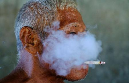 FILE PHOTO: A worker smokes a cigarette during a break at a fabric factory in Solo, Indonesia Central Java province, August 11, 2016. REUTERS/Beawiharta/File Photo