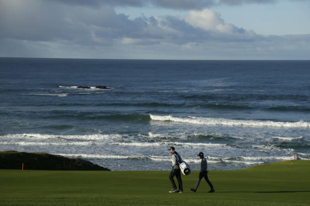 Scott Langley walks with his caddie down the 10th fairway of the Pebble Beach Golf Links during the third round of the AT&T Pebble Beach Pro-Am golf tournament Saturday, Feb. 9, 2019, in Pebble Beach, Calif. (AP Photo/Eric Risberg)