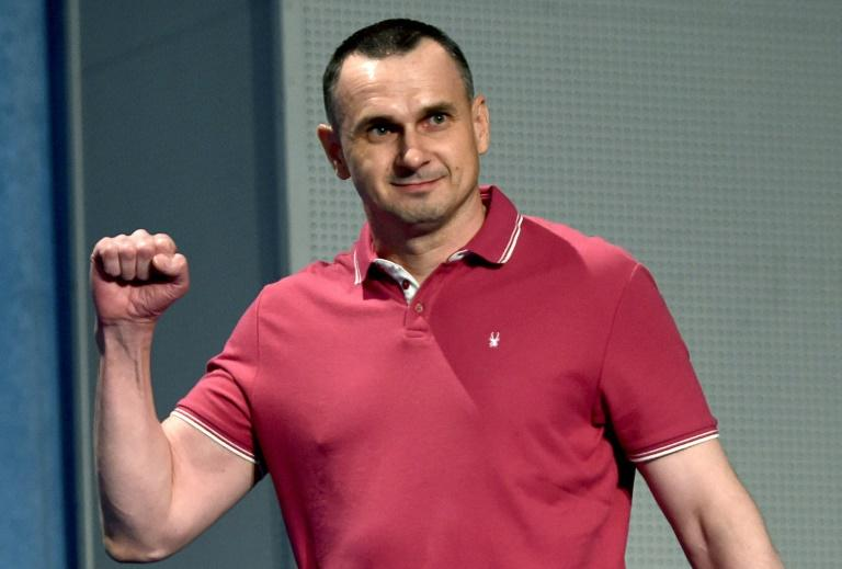 Freed Ukrainian film director Oleg Sentsov greets journalists on Tuesday