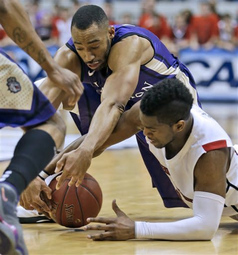 Northeastern guard Jonathan Lee, right, struggles to control the ball as James Madison guard A.J. Davis, left, closes in during the first half of the CAA Conference tournament championship NCAA college basketball game in Richmond, Va., Monday, March 11, 2013. (AP Photo/Steve Helber)
