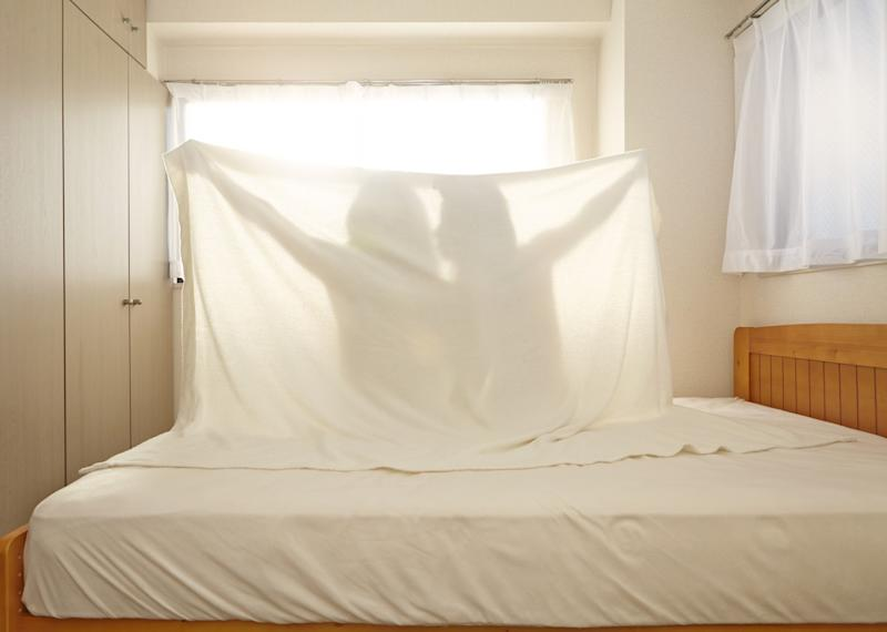 Couple in bed holding up sheet