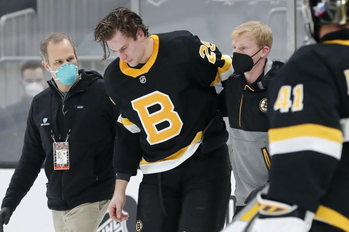 FILE - Boston Bruins' Brandon Carlo is helped off the ice during the first period of an NHL hockey game against the Washington Capitals in Boston, in this Friday, March 5, 2021, file photo. The Boston Bruins and Washington Capitals already have bad blood built up going into their first-round playoff series that starts Saturday night, May 15. (AP Photo/Michael Dwyer, File)