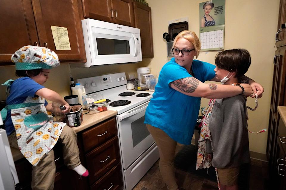 In this July 28, 2021 photo, Christina Darling and her sons, Brennan, 4, left, and Kayden, 10, prepare a snack at home in Nashua, N.H. Darling and her family have qualified for the expanded child tax credit, part of President Joe Biden's $1.9 trillion coronavirus relief package.