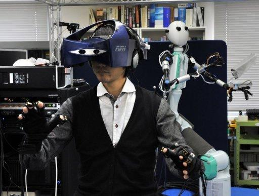 """An operator -- wearing a special HMD and a pair of gloves -- controls the """"Telesar V"""" (right) that was developed by Keio University's Graduate School professor Susumu Tachi (not in the picture) at his laboratory in Yokohama, suburban Tokyo. The robot that mimics the movements of its human controller is bringing the Hollywood blockbuster """"Avatar"""" one step closer to reality"""