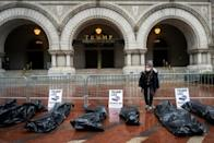"""Participants in a """"People's Motorcade"""" stop at the Trump International Hotel to deliver fake body bags during a protest against the administration's response to the COVID-19 pandemic in Washington, DC"""