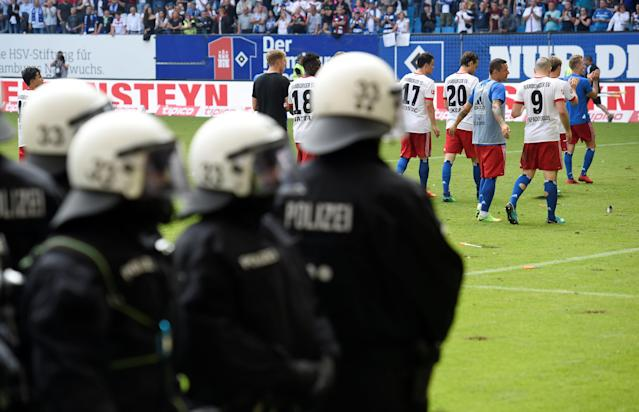 Soccer Football - Bundesliga - Hamburger SV v Borussia Moenchengladbach - Volksparkstadion, Hamburg, Germany - May 12, 2018 Hamburg's Kyriakos Papadopoulos and team mates look dejected during their lap of honour as riot police on the pitch at the end of the match REUTERS/Fabian Bimmer DFL RULES TO LIMIT THE ONLINE USAGE DURING MATCH TIME TO 15 PICTURES PER GAME. IMAGE SEQUENCES TO SIMULATE VIDEO IS NOT ALLOWED AT ANY TIME. FOR FURTHER QUERIES PLEASE CONTACT DFL DIRECTLY AT + 49 69 650050