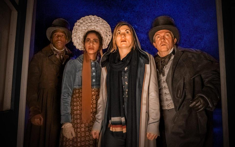 Ryan, Yaz, the Doctor, and Graham, all wearing period 1800s clothing, apart from the Doctor, stand soaked with rain in a brightly lit doorway in Doctor Who.
