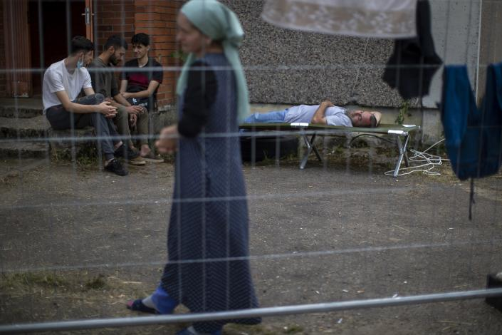 A woman walks past migrants from Iraq resting at the refugee camp in the village of Verebiejai, some 145km (99,1 miles) south from Vilnius, Lithuania, Sunday, July 11, 2021. Migrants at the school in the village of Verebiejai, about 140 kilometers (87 miles) from Vilnius, haven't been allowed to leave the premises and are under close police surveillance. Some have tested positive for COVID-19 and have been isolated in the building. (AP Photo/Mindaugas Kulbis)