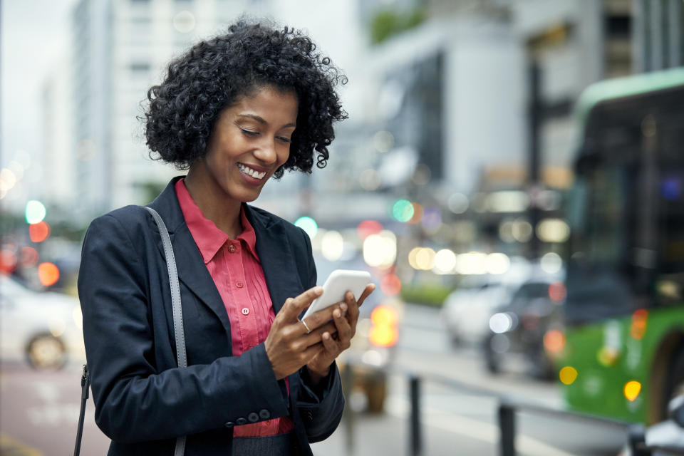 Smiling young businesswoman surfing net on mobile phone. Female commuter is standing in financial district. She is having black curly hair.