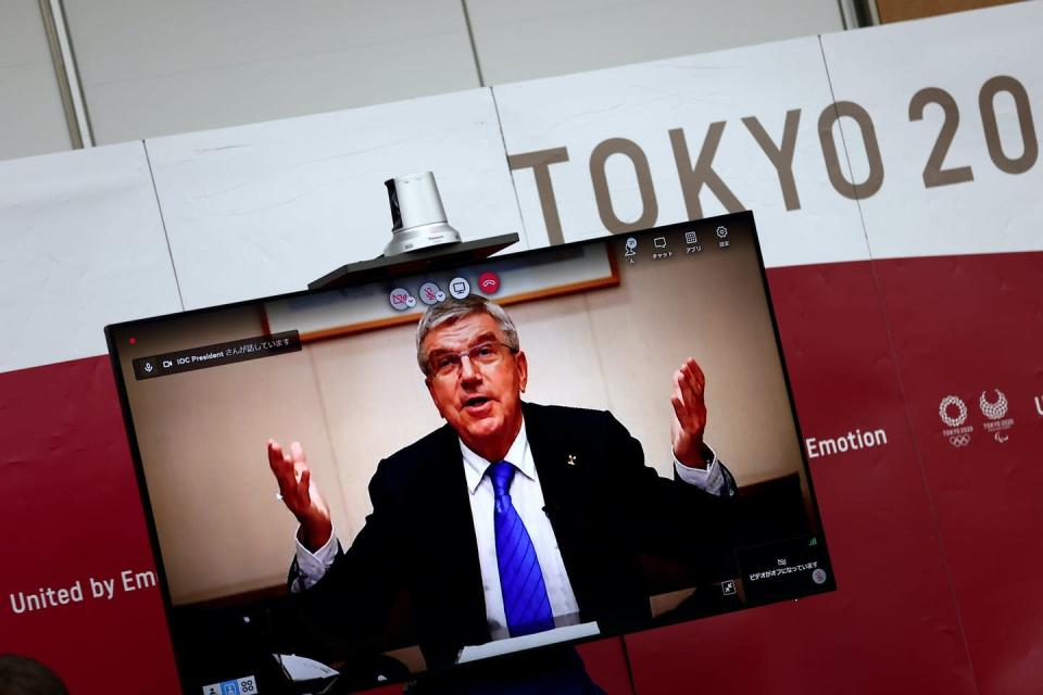 Bach raises his hands while appearing on a TV screen at a news conference in Tokyo.