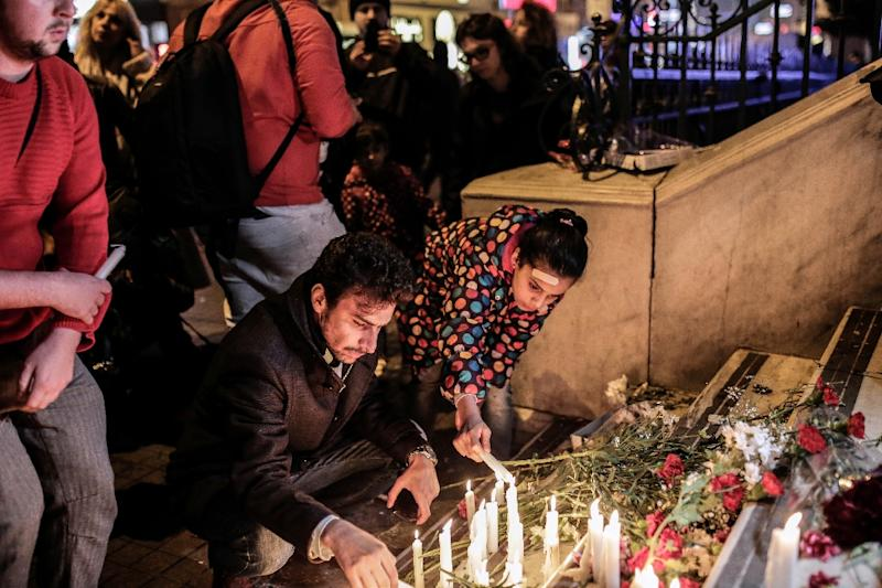 People hold candles and lay floral tributes at the French consulate in Istanbul on November 14, 2015 (AFP Photo/Yasin Akgul)