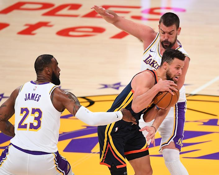 Feb 28, 2021; Los Angeles, California, USA;  Golden State Warriors guard Stephen Curry (30) is defended by Los Angeles Lakers forward LeBron James (23) and center Marc Gasol (14) as he takes the ball down court in the first quarter of the game at Staples Center. Mandatory Credit: Jayne Kamin-Oncea-USA TODAY Sports