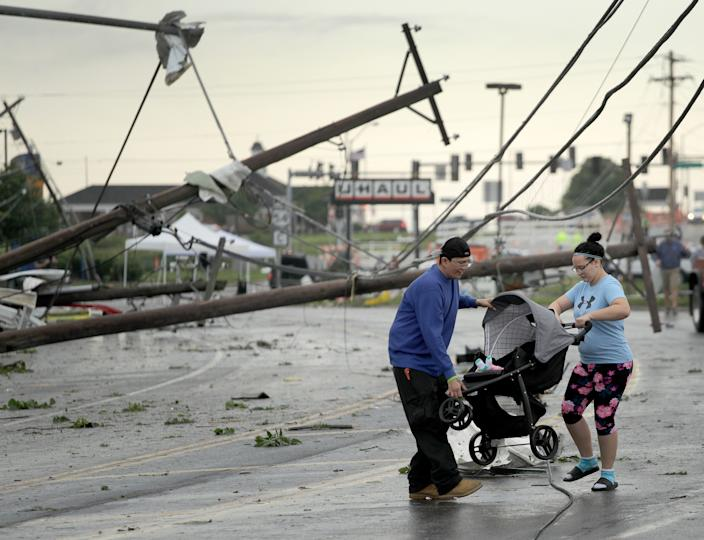 Jessica Rodgers and a neighbor Ray Arellana carry a stroller carrying Rodgers' sister Sophia Rodgers over downed power lines as they head to Rodgers' mother's apartment to check on damage on May 23, 2019 after a tornado tore though Jefferson City. (AP Photo/Charlie Riedel)