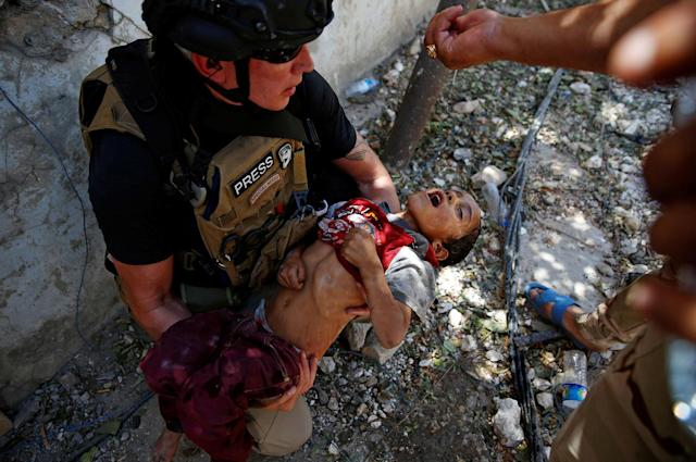 <p>Iraqi soldiers from 9th Armoured Division give drops of water to a dehydrated child rescued earlier by soldiers at the frontline, during the ongoing fighting between Iraqi forces and Islamic State militants near the Old City in western Mosul, Iraq, June 13, 2017. (Photo: Erik De Castro/Reuters) </p>