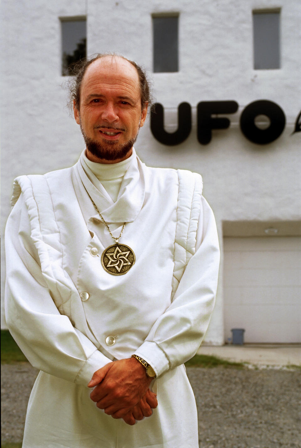 Claude Vorilhon, the spiritual leader of the Raelians, wears white robes and a large medallion necklace while standing outside a large white building with the sign 'UFO land' in Valcourt, Quebec, Canada in 1997