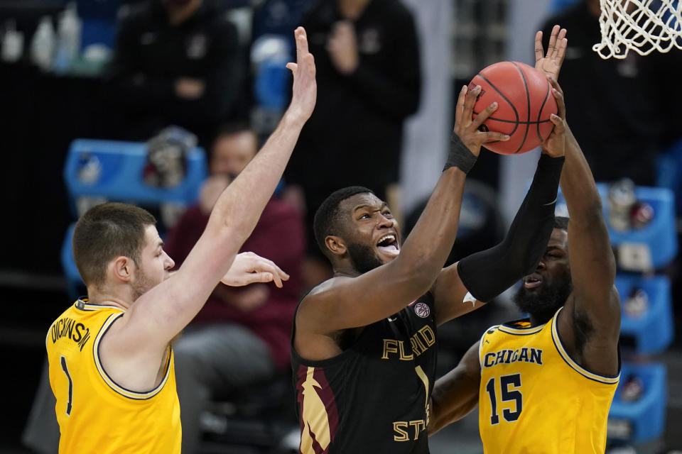Florida State forward RaiQuan Gray, center, shoots between Michigan center Hunter Dickinson, left, and guard Chaundee Brown, right, during the second half of a Sweet 16 game in the NCAA men's college basketball tournament at Bankers Life Fieldhouse, Sunday, March 28, 2021, in Indianapolis. (AP Photo/Jeff Roberson)