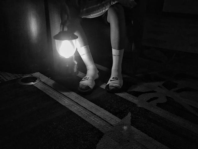 A boy sits with a lantern flashlight after a hotel lost power during Hurricane Irma. (Photo: Holly Bailey/Yahoo News)