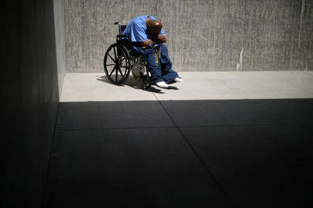 An inmate sits in the yard of a cellblock which mainly houses prisoners with cognitive decline, Alzheimer's, and dementia, at the California Health Care Facility in Stockton, California, U.S., May 24, 2018. REUTERS/Lucy Nicholson