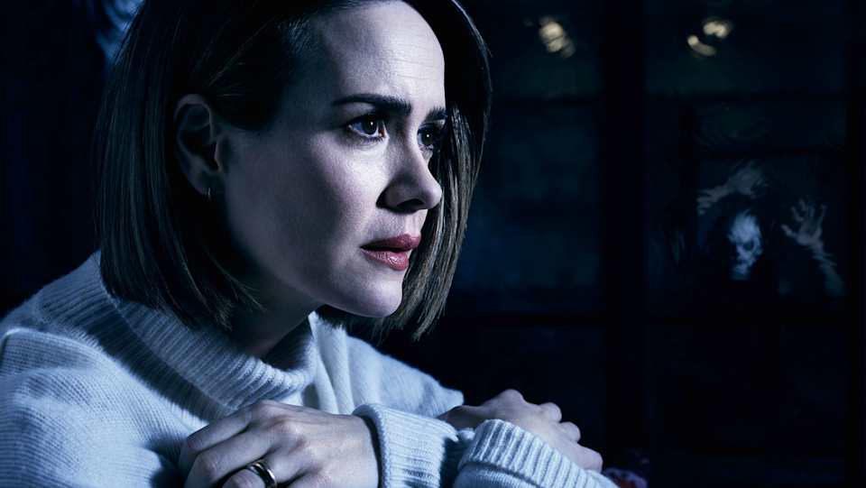 Sarah Paulson looks frightened while a clown stalks her in the background in this image from American Horror Story: Cult.