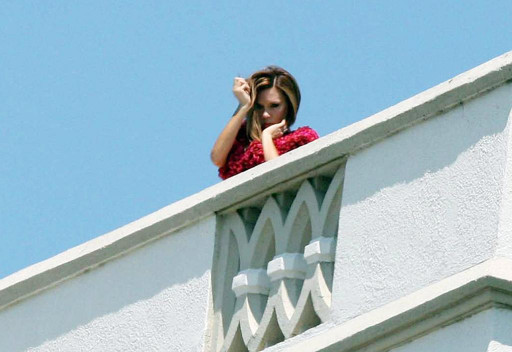 "In yet another fruitless attempt to be taken seriously as a fashion icon, Victoria Beckham pops an awkward pose in a fluffy red frock during a top secret photo shoot atop the Chateau Marmont in Los Angeles. <a href=""http://www.infdaily.com"" target=""new"">INFDaily.com</a> - May 27, 2008"