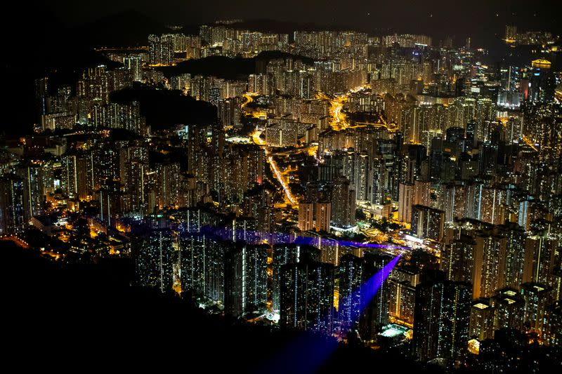 FILE PHOTO: Laser beams, coming from the residential buildings in Kowloon district, are seen as anti-government protesters gather at Lion Rock, in Hong Kong