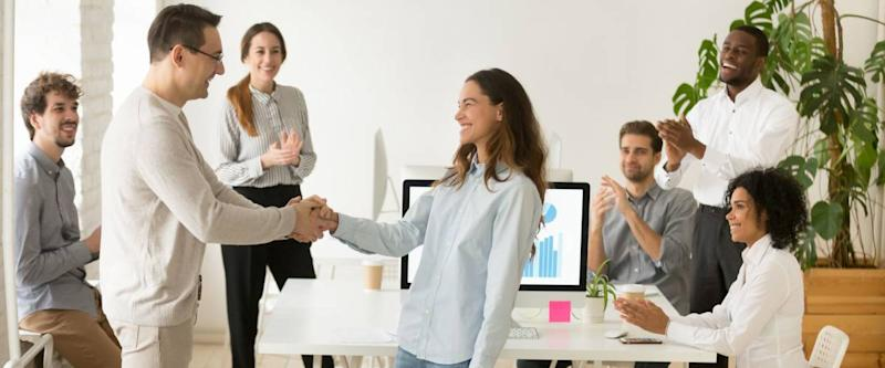 Boss shaking hand of young shy woman congratulating successful employee with promotion, hiring intern