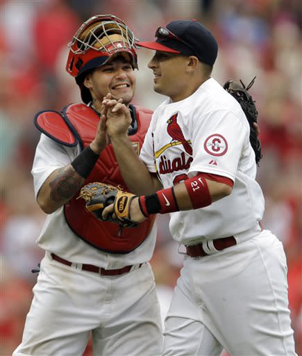 St. Louis Cardinals' Yadier Molina, left, and Allen Craig celebrate after the Cardinals' 3-2 victory over the San Diego Padres in a baseball game Sunday, July 21, 2013, in St. Louis. (AP Photo/Jeff Roberson)