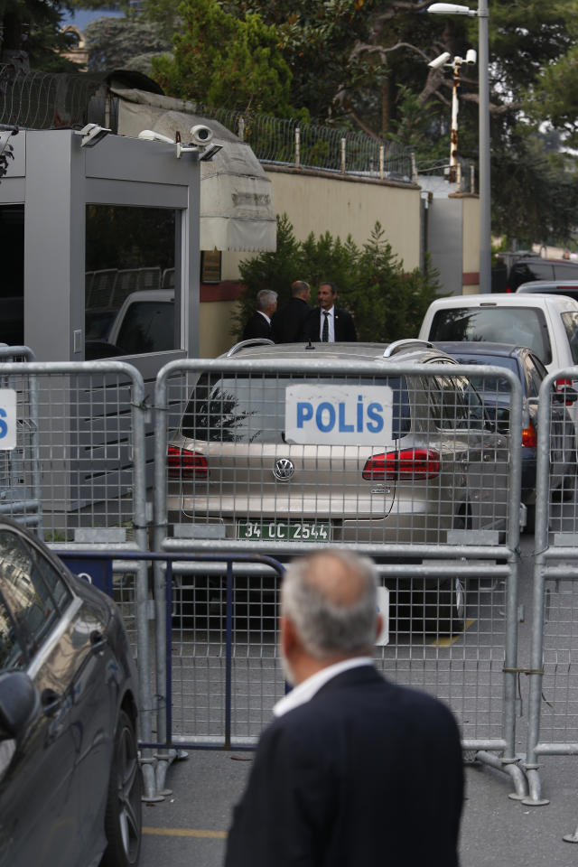 Members of the security personnel guarding Saudi Arabia's consulate are seen behind barriers blocking the road leading to the diplomatic mission, in Istanbul, Tuesday, Oct. 23, 2018. The Turkish president is expected to announce details Tuesday of his country's investigation into the killing of Saudi writer Jamal Khashoggi, as skepticism intensified about Saudi Arabia's account that he died accidentally in its consulate in Istanbul. (AP Photo/Lefteris Pitarakis)