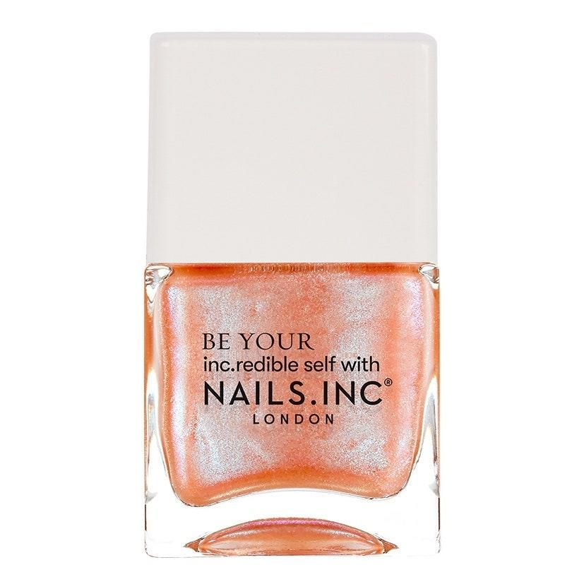 """<p>With a name like Are We Having Wine?, you might expect this new Nails Inc shade to be in the burgundy family, but the sparkling-rosé-inspired shade is actually an ideal way to wear one of our favorite color trends of the season, apricot shimmer. </p> <p>Nail artist of <a href=""""https://www.instagram.com/julieknailsnyc/"""" rel=""""nofollow noopener"""" target=""""_blank"""" data-ylk=""""slk:Julie Kandalec"""" class=""""link rapid-noclick-resp"""">Julie Kandalec</a> of of Julie K Nail Artelier in New York City says now is the time to take your favorite colors and wear them in the most extra way. """"This summer, it's all about all the things — like shimmer plus color,"""" she says, calling this shade a """"super-fun look."""" </p> <p>Peachy colors will always peak in popularity during the summer, but we love the coolness (literally and tonally) a hint of silver iridescence brings to a warm, soft orangey-pink to separate it from the flat, creamy manicure masses. </p>"""
