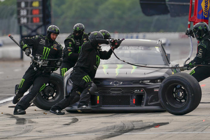 The pit crew for Kurt Busch (1) works on the car during a stop during a NASCAR Cup Series auto race at Pocono Raceway, Saturday, June 26, 2021, in Long Pond, Pa. (AP Photo/Matt Slocum)